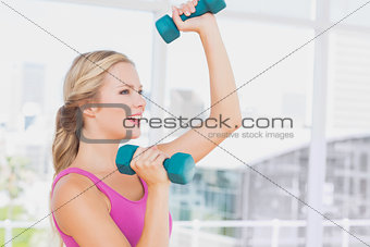 Fit blonde lifting dumbbells and smiling