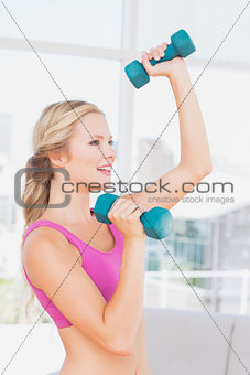 Toned blonde lifting dumbbells and smiling