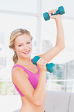 Athletic blonde lifting dumbbells and smiling