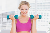 Cute blonde lifting dumbbells and smiling