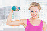 Happy blonde lifting dumbbell and flexing