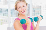 Happy blonde lifting dumbbells smiling at camera