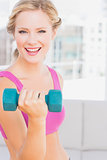 Blonde lifting dumbbells and smiling at camera