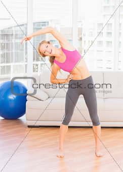 Fit blonde smiling at camera while stretching