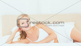 Beautiful blonde lying on her bed smiling at camera
