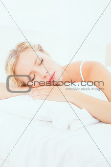 Attractive young blonde sleeping on her bed
