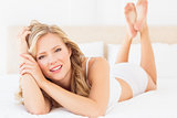 Happy young blonde lying on her bed looking at camera
