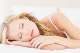 Natural young blonde lying on her bed asleep