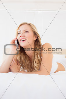 Cute young blonde on the phone lying on bed