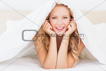 Attractive blonde smiling at camera from under the duvet