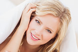 Pretty young blonde smiling at camera from under the duvet