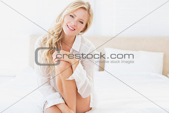 Beautiful young blonde in white shirt smiling at camera sitting on bed