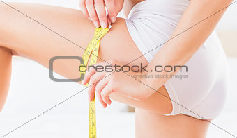 Toned woman measuring her thigh