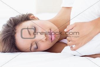 Sleeping pretty brunette lying on bed hugging pillow
