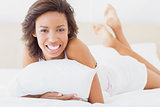 Smiling pretty brunette lying on bed holding pillow