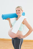Pregnant blonde smiling at camera holding exercise mat