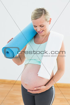 Pregnant blonde smiling at bump holding exercise mat