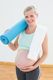 Pregnant woman smiling at camera holding exercise mat