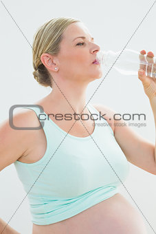 Pregnant woman drinking bottle of water