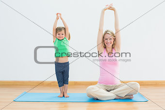 Pregnant mother and daughter doing yoga together