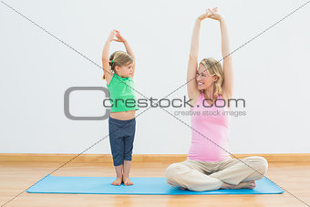 Pregnant smiling mother and daughter doing yoga together