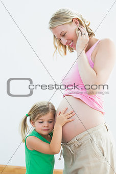 Little girl listening to blonde mothers pregnant belly