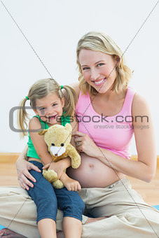 Pregnant woman smiling at camera with her young daughter