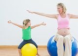 Pregnant woman bouncing on exercise ball with young daughter