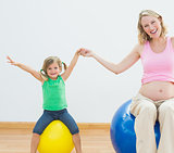 Happy pregnant woman bouncing on exercise ball with young daughter