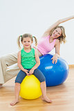 Happy pregnant woman exercising on exercise ball with young daughter