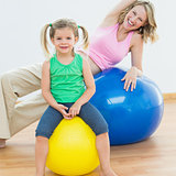 Smiling pregnant woman exercising on exercise ball with young daughter
