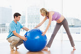 Blonde pregnant woman exercising with trainer and ball