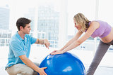 Happy pregnant woman exercising with trainer and ball
