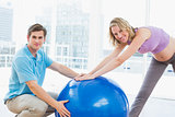 Smiling pregnant woman exercising with trainer and ball