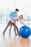 Cheerful pregnant woman exercising with trainer and ball