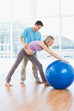 Trainer exercising with pregnant client and exercise ball