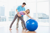 Trainer exercising with smiling pregnant client and exercise ball