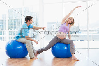 Trainer exercising with blonde pregnant client on exercise balls