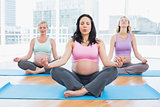 Meditating pregnant women in yoga class sitting on mats
