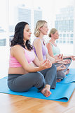 Meditating pregnant women in yoga class