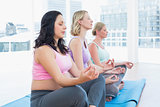 Relaxed pregnant women meditating in yoga class