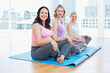 Happy pregnant women sitting in yoga class