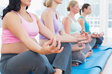 Calm pregnant women meditating in yoga class