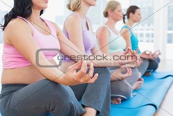 Calm pregnant women meditating in yoga class