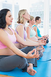 Content pregnant women meditating in yoga class