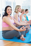 Content pregnant women meditating in yoga class with one smiling at camera