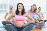 Happy pregnant women in yoga class holding their bumps