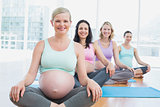 Happy pregnant women in yoga class sitting on mats