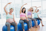 Pregnant women sitting on exercise balls stretching arms