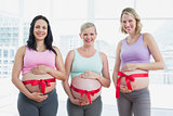 Happy pregnant women standing with red bow around bumps